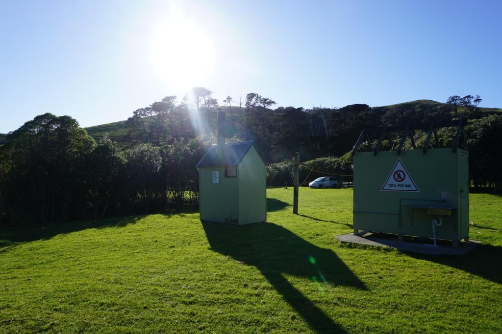 Sanitärgebäude des Campingplatzes: Plumpsklo (links) und kalte Dusche mit Waschbecken (rechts)