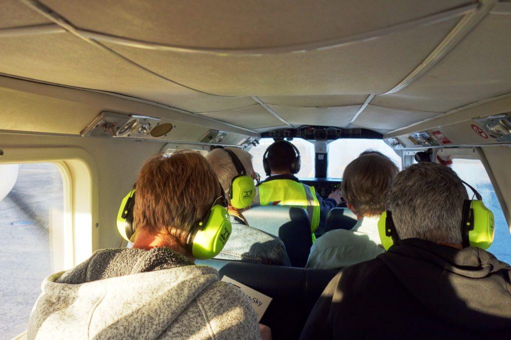 Der Pilot sitzt vorne links und die Fluggäste daneben bzw. dahinter