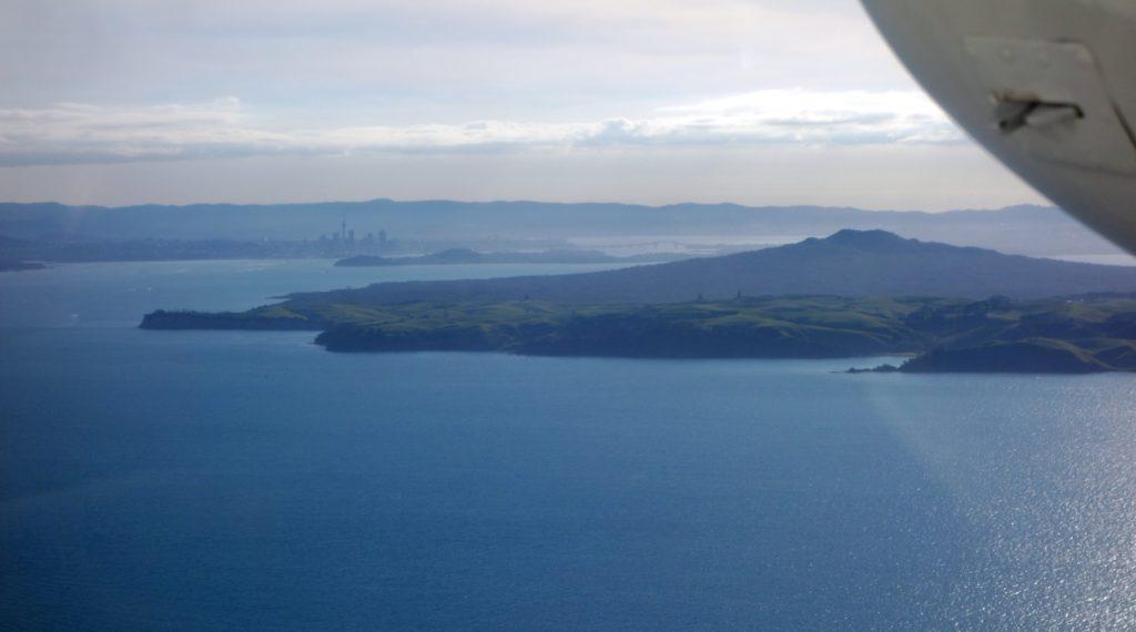 Luftbild von Rangitoto (vorne) und Auckland's Skyline sowie Harbour Bridge (hinten)