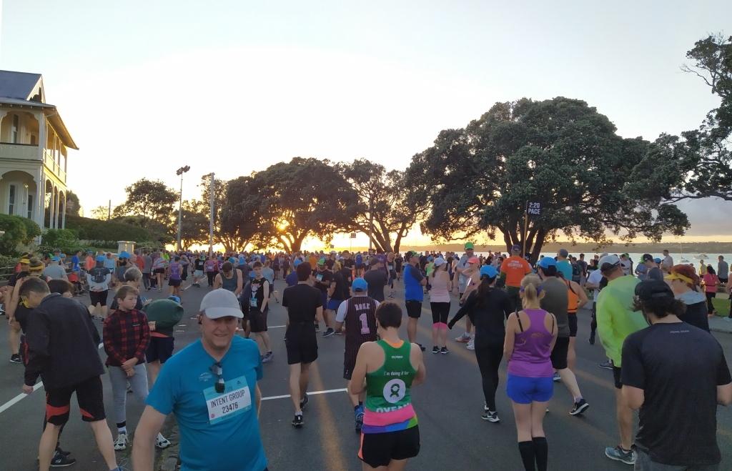 Athleten sammeln sich am Start. Wir Langsamen starten so weit hinten, dass die Startlinie noch nicht mal im Sichtfeld ist. Der 2:20 Pacer steht mittig recht mit orangenem T-Shirt