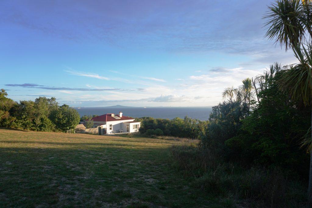 Bunkhouse mit dem Vulkan Rangitoto in Hintergrund. Aucklands Skyline kann noch erahnt werden.
