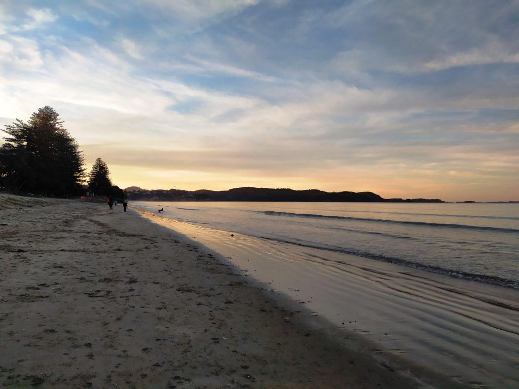 Die Nacht bricht herein am Strand von Orewa